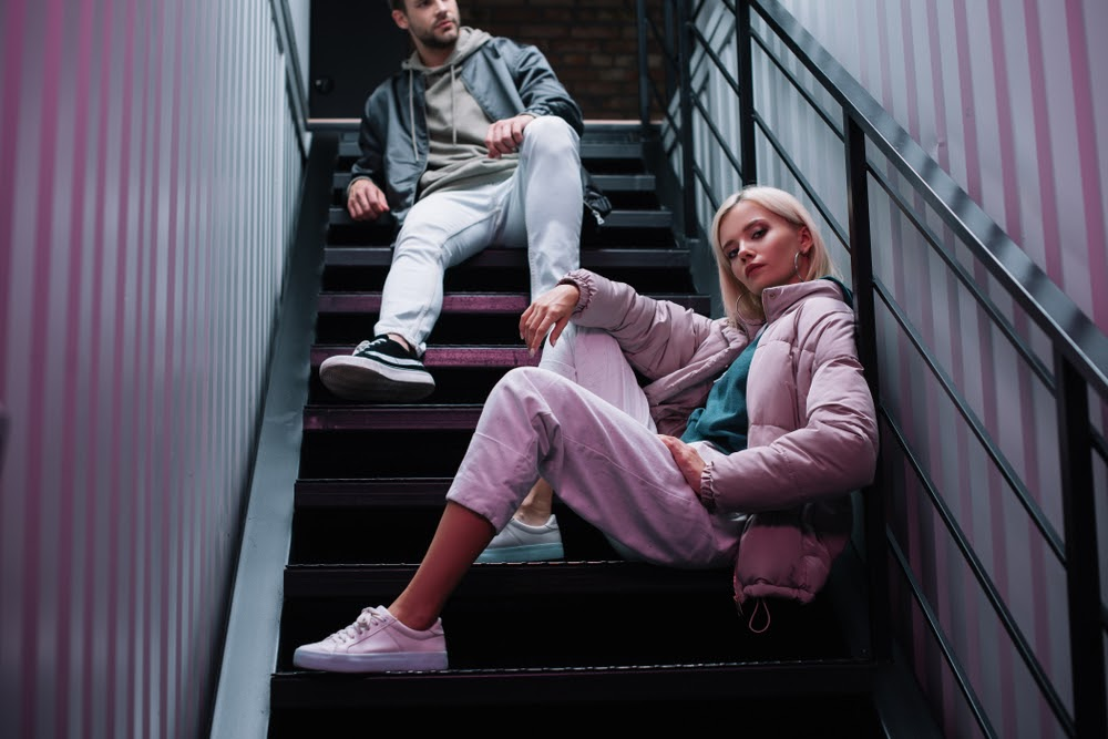 woman and man sitting on stairs wearing hoodies